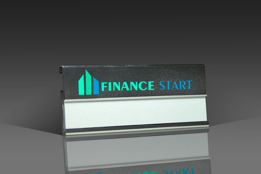 Metal Name Badge NMSS, with professional printing on the display area above  the insert (e g  logo/slogan)